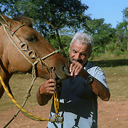 Subsistence farmer examining a horse in northern Goias State, Brazilian Highlands.