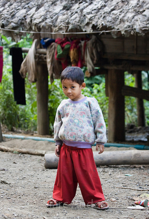 Young boy standing in front of his village home, Mae Sam Laep, Mae Hong Son Province, Thailand