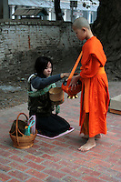Young Novice Collecting Alms - In Buddhism, giving alms is a show of respect given by a lay Buddhist to a Buddhist monk. It is not charity as presumed by Western eyes. It is closer to a symbolic connection to the spiritual and to show humility and respect.  The visible presence of monks is a stabilizing influence in Lao society. The act of alms giving assists in connecting lay people to the monk and what he represents.