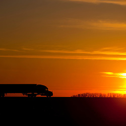 As the sinks towards the horizon, a semi tractor trailer truck rolls north on I-55 in Central Illinois.