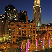 This photography image shows downtown Boston with the Custom House Tower, art installation Light Blades, and the Rose F. Kennedy Greenway near Faneuil Hall Marketplace. Every night, twelve vertical glass and steel sculptures illuminate the Wharf District Parks plaza between Milk and India Streets with joyful colors. This unique system of LED lights is programmed to show up to 16.7 million different colors, along with an array of patterns, speed and intensity. The Custom House Tower was the first real skyscraper in Boston, and a very historic and beautiful building with four illuminated clocks in its elegant spire.<br />