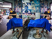 """06 FEBRUARY 2017 - BANGKOK, THAILAND: A mirror reflects a barber cutting a customer's hair in a small barbershop in what used to be known as Kalabok Market under the Phra Khanong Bridge in the Phra Khanong district of Bangkok. Kalabok is the Thai word for hairdresser and the market was called Kalabok because there were many barbershops and hairdressers under the bridge. In 1985, the city changed the name of the market to """"Singha Market."""" There are still about 10 small men's barbershops, most with just one barber, and four women's salons, most with one hairdresser,  under the bridge.      PHOTO BY JACK KURTZ"""