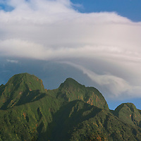 A large cloud hangs over Mount Sabinyo, an extinct volcano in the Virunga Mountains which straddle the border region of Rwanda, Uganda and the Democratic Republic of Congo