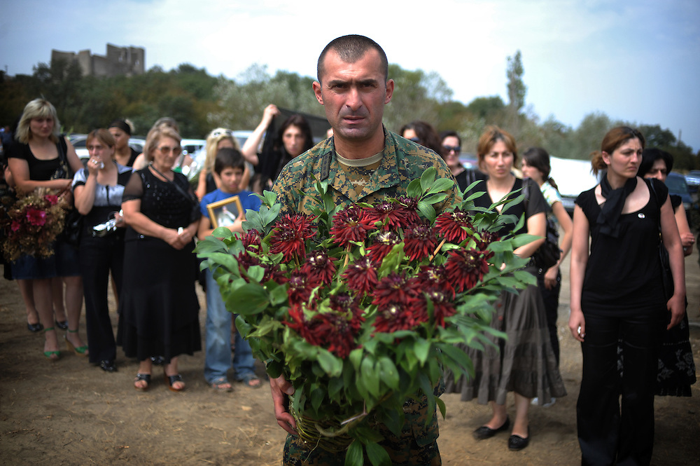 A Georgian soldier holds flowers during funerals for Georgian soldiers killed in South Ossetia during the conflict with Russia on August 30, 2008 at the Mukhadgverdi cemetery, west of Tbilisi. Russian President Dmitry Medvedev called today on European governments to send more observers to Georgia, a Kremlin statement said.