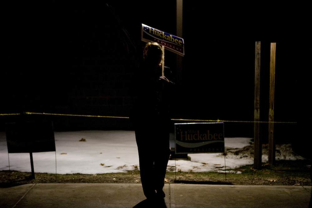 A supporter with a sign stands in the shadows as Republican presidential hopeful and former Arkansas governor Mike Huckabee campaigns at a polling station in Londonderry, N.H., on Tuesday, Jan. 8, 2008.