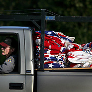 Veteran Mike Snydsman, who was a door gunner during Vietnam, drives a pickup loaded with flags during installation on the Avenue of Flags on Wednesday November 8, 2006 at Tahoma National Cemetery.  Joshua Trujillo / Seattle Post-Intelligencer