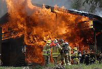 Jackson Hole firefighters coordinate efforts to extinguish a house fire at 725 Snow King Drive. The fire consumed the front of the duplex within minutes and called out the bulk of Jackson's volunteer fire department.