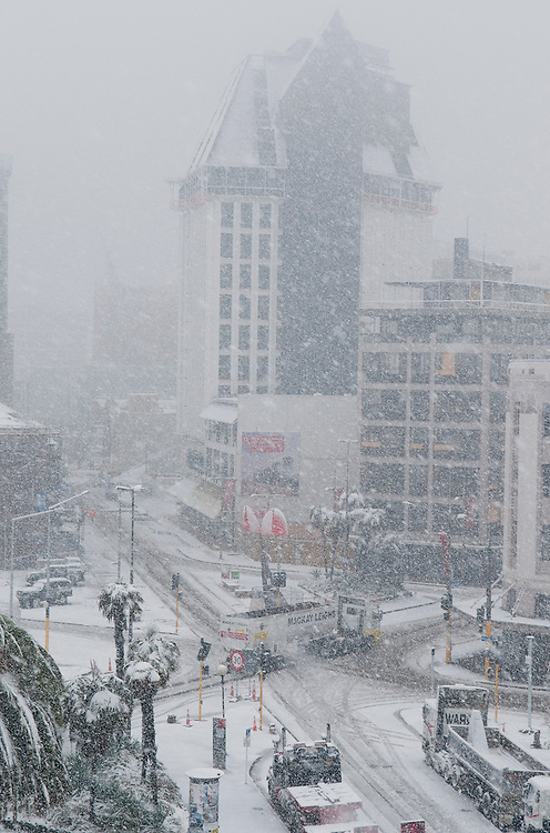 A demolition truck crawls through the Manchester and High Street intersection as snow falls in the CBD, Christchurch, New Zealand, Wednesday June 6, 2012. Credit: SNPA /  David Alexander.