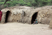 Africa, Tanzania, Maasai tribe an ethnic group of semi-nomadic people Boy sits in front of his mud and straw dwelling