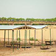 LÉGENDE: Les anciens étalages que les vendeuses utilisaient avant la construction des nouveaux étalages. En arrière plan, on peut voir un pont que les usagers empruntent au quotidien pour se rendre facilement au marché de Chagoua. LIEU: Marché de Chagoua, N'Djaména, Tchad. PERSONNE(S): N/A.