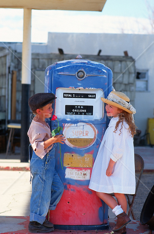 Young boy holding a rose looking at a young girl, leaning against a rural gas pump