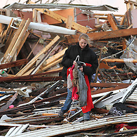 A woman salvages belongings after her home was destroyed by a tornado in Henryville, Indiana Friday afternoon. One person was reported to be killed in the town..Chris Bergin/SWAT Chasers