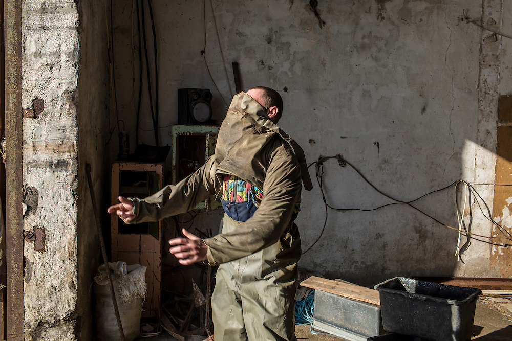 A fisherman, Pavel, puts on a rubber suit before venturing out to sea on Saturday, April 11, 2015 in Siedove, Ukraine.