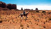 Horseman riding in the vast landscape of Monument Valley, Arizona.