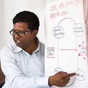 CAPTION: Dr Ram Chandra Soren is the Medical Officer-in-Charge in this area. Here, he is training Community COPE members on how efficiency can be improved. This involves consideration of how best to draw up a work plan, how to gather knowledge, how work can then be done, how follow-ups can be done, how analysis of what's been done should happen, how information gathering should again happen, and so on. The cycle aims for quality improvement, and is continuous, not a one-time thing. Benchmarks are regularly set and reviewed. LOCATION: Pawra (village), Ghatshila (block), Purbi Singhbhum (district), Jharkhand (state), India. INDIVIDUAL(S) PHOTOGRAPHED: Dr Ram Chandra Soren.