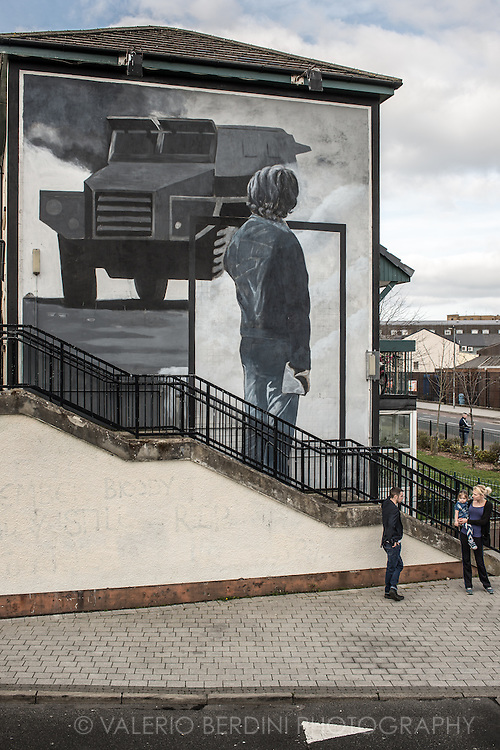 A family chats in front of a large mural in the Bogside area of Derry.