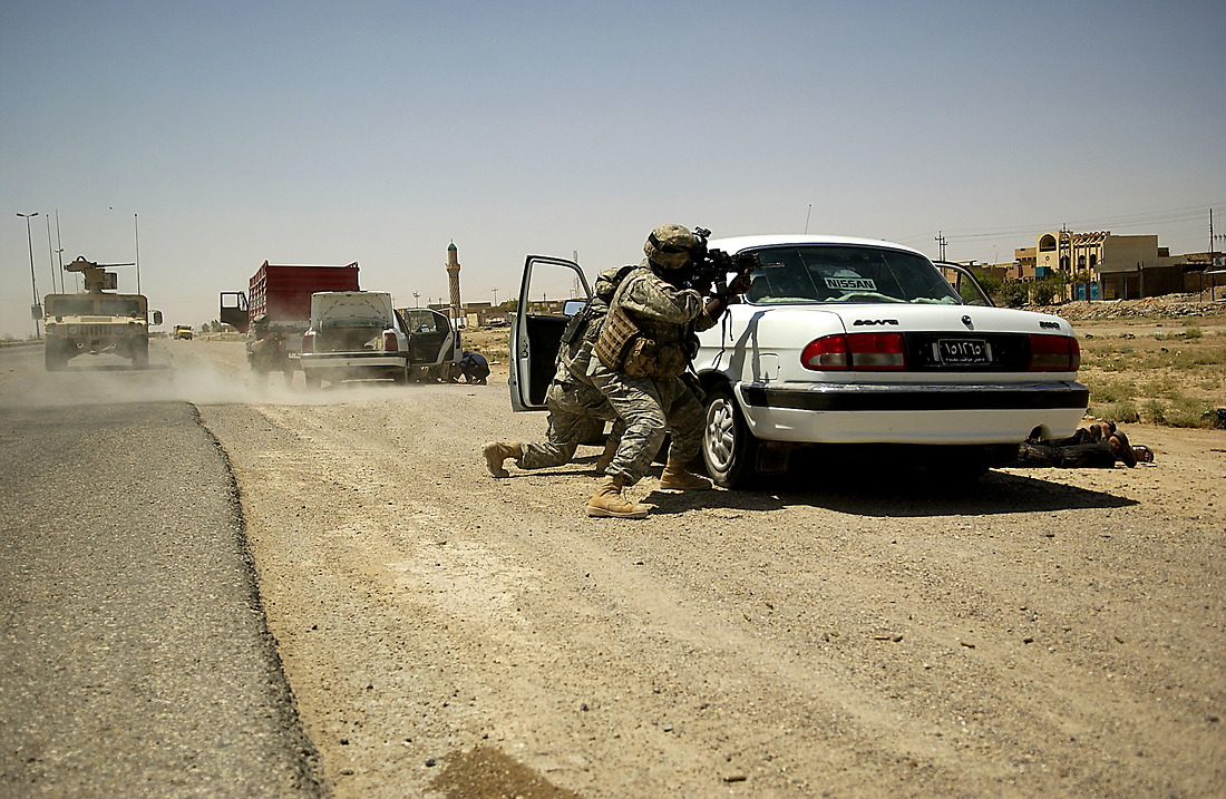 Soldiers from Bravo Company, 2nd Battalion, 6th Infantry Regiment, 1st Armored Division, Baumholder, Germany, take cover behind vehicles and return fire on Anti Iraqi Forces on August 16, 2006. The soldiers came under fire during a Traffic Control Point (TCP) on Alternate Supply Route Michigan in Tameem, Ramadi, Iraq.  SGT Nathan McCool was shot in the back and is recovering from his injury. TCP's are performed by pulling over random vehicles, searching the vehicle and it's occupants for weapons or explosives being transported into the city. — © TSgt Jeremy Lock/