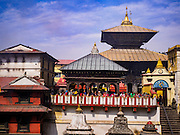 07 MARCH 2017 - KATHMANDU, NEPAL: The Pashupatinath Temple, above the ghats on the banks of the Bagmati River in Kathmandu. It is the oldest Hindu temple in Kathmandu. The Bagmati River runs through the complex. It is Nepal's most holy river, and this stretch of the river is like Varanasi in India. The river bank is lined with cremation ghats. Many Hindus, from both Nepal and India, make pilgrimages to Pashupatinath.     PHOTO BY JACK KURTZ