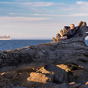 A young lad sits in the late afternoon sun, perched on a large driftwood log washed up on the shore along Ediz Hook. The Hook is the sandspit the Strait of Juan de Fuca which creates Port Angeles Harbor.