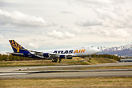 Atlas Air cargo jet landing at Ted Stevens Anchorage International Airport in Southcentral Alaska with the Chugach Mountains in the background. Spring. Afternoon.
