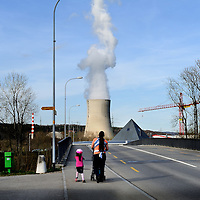 Mother with her children strolling along a road, with the cooling tower of the G&ouml;sgen Nuclear Power Plant (Kernkraftwerk G&ouml;sgen) rising behind. <br /> The Swiss are due to vote shortly in a referendum whether to quit nuclear power, which via its five reactors, on four sites, provide almost 40% of the country's power