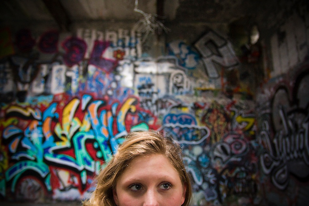 Anna Reiser walks among graffiti art in an abandoned warehouse in Blakely Harbor Park on Bainbridge Island, Washington. The park is the former site of Port Blakely Mill, which was one of the world's largest sawmills in the late 19th century.