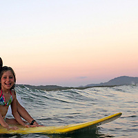 Central America, Costa Rica, Tamarindo. Mother and daughter on surfboard in Costa Rica.