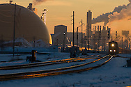 An eastbound train of coal threads its way through the industrial area of Clinton, IA. Clinton is home to several large corn processing facilities, and soon, a large co-generation plant meant to produce ethanol. The large dome is for storage of the plant's fuel.