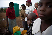 """Adults and Children in the suburb of Budiriro outside of Harare queue to collect clean water in containers brought to collection points where water bowsers have been supplied by NGO's such as UNICEF. ..As of 30 May 2009, there were 98 424 suspected cases, including 4 276 deaths reported by the Ministry of Health and Child Welfare (MoHCW) of Zimbabwe since August 2008. Fifty-five out of 62 districts in all 10 provinces were affected. in December 2008, Robert Mugabe declared that """"there is no cholera"""" in Zimbabwe. Failing sanitation and lack of water supply were to blame, workers responsible claimed they had not been paid by the government for several months."""