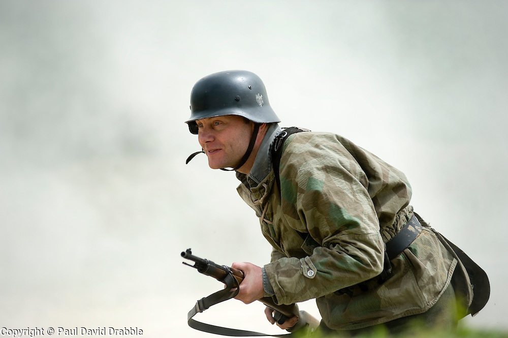 Reenactor from Northern World War Two Association, dressed as a member of the elite Gross Deutschland division moves forward through smoke during a private 24hr excerise, held at Sutton Grange, near Ripon in Yorkshire. He is wearing the Iconic German Steel Helmet (Stahlhelm) with Splinterpatern Camouflage clothing and crrying a Mauser K98 Kar Rifle<br />  15  May 2010 .Images &copy; Paul David Drabble.