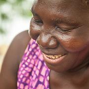LÉGENDE: Le visage d'une vendeuse de poissons souriante assit, elle découpe son poisson en plusieurs morceaux. LIEU: Marché de Chagoua, N'Djaména, Tchad. PERSONNE(S): Une vendeuse de poissons assis.