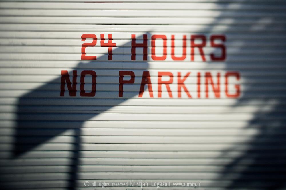 24 hours no parking painted on a garage door