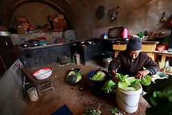 A picture made available on 06 November 2012 of 71-year-old farmer Fang Yili washing vegetables in her cave home or 'yaodong' in the rural outskirts of Yan'an city, Shaanxi Province China, 05 November 2012. The 'yadong' or cave dwellings are typical in the plateaus of northern China in Shaanxi Province where many of Yan'an's rural population still live in. They are mostly carved out from the yellow earth of the Loess hillsides and are about seven to eight metres deep with height and width of three metres. Former Communist leader Mao Zedong and his comrades are known to have hid in these cave homes during the civil war between the communists and nationalists in 1936 to 1948 as they battle the Kuomintang forces. Chao has lived in his cave home in the Loess mountains of Yan'an for more than 60 years, mostly in poverty and hardship as a farmer and was one of the few to have lived through the period of turmoil during the civil war. China's new leaders slated to take over during the 18th National Congress beginning on 08 November are likely to face mounting pressures to tackle the country's rising income inequalities between urban and rural areas that are often the source of simmering resentment and growing unrests on the grassroot level.