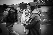 A mother carries her new born baby on her way to a bus at a makeshift camp near Tovarnik's train station, Croatia.<br />