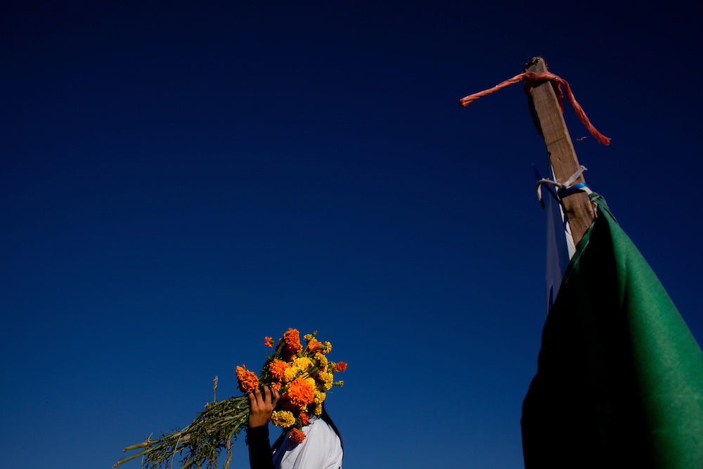 "A woman covers her face with flowers at the grave site of her brother on ""Day of the Dead"" in November. The boy had been kidnapped and was later found dead."