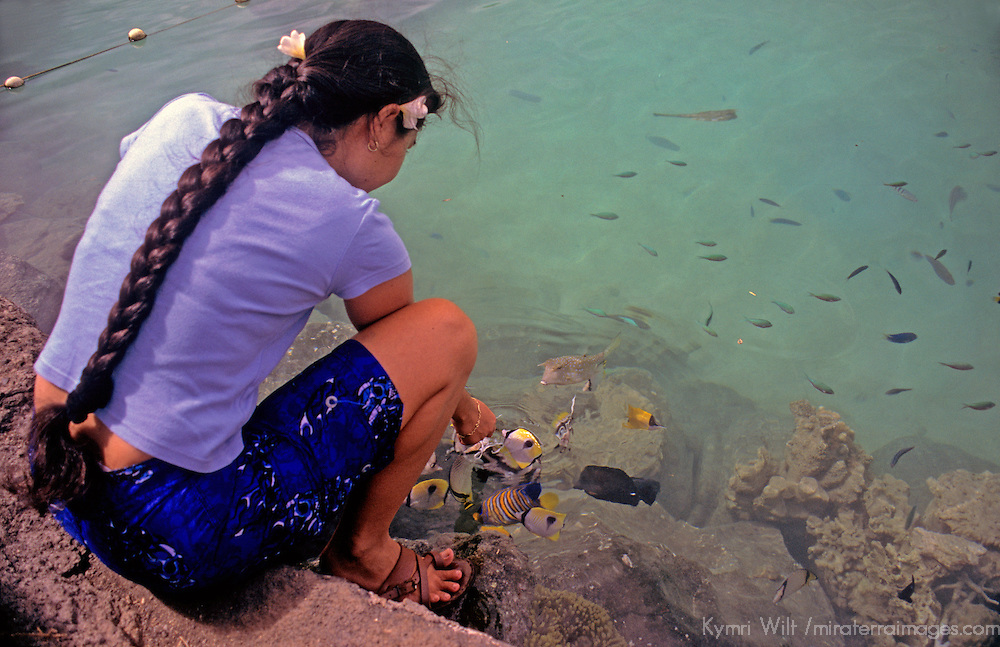 Oceania, South Pacific, French Polynesia, Tahiti. Polynesian woman feeds tropical fish.