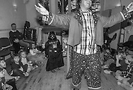 Ben dressed as Darth Vader looks on as Arty Smarty the clown entertains children at his 5th birthday party at the town hall in Ivinghoe, Saturday, March 14,  2016.  It was in Kenya, on an assignment photographing Masaai mothers and children, where I was reminded of the power of the familiar and the mundane.Amid the rugged landscapes and the cattle-herding families whose lives still revolve around ancient rhythms, I began to wonder about my own attitudes. Why did I think mothers in this different and exotic environment were worthy of being documented? Why did I think motherhood in my own world lacked that luster? Why is the remote more valuable to a photographer than the world right around them? And I realized I had turned a blind eye to the profound, complex story right next to me: in the school runs, the trips to the store, the swimming lessons and the countless birthday parties and field trips.It is the world I navigate every day with my two young sons.This project has let me see photographs where before I thought there were none. It has allowed me to see the universality of my life and how it is reflected in so many other lives.