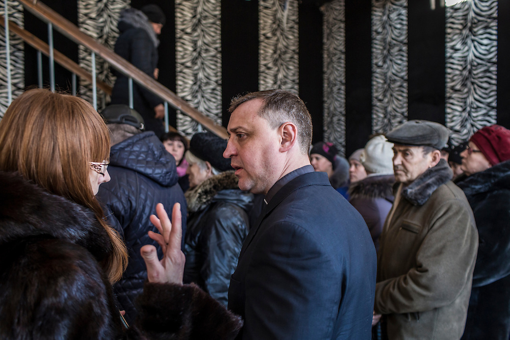MARIINKA, UKRAINE - FEBRUARY 20, 2016:  Pastor Sergei Kosyak, center, talks with congregants after a service at the Christian Help Center of the Church of the Transfiguration in Mariinka, Ukraine. The Donetsk suburb has been the scene of some of the heaviest fighting recently between Ukrainian forces and pro-Russian rebels. CREDIT: Brendan Hoffman for The New York Times