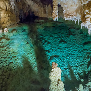 "Halo Lake panorama, Caverns of Sonora, Sutton County, Texas, USA. The world-class Caverns of Sonora have a stunning and sparkling array of speleothems (helictites, stalactites, stalagmites, flowstone, coral trees, and other calcite crystal formations). National Speleological Society co-founder, Bill Stephenson said, after seeing it for the first time, ""The beauty of Caverns of Sonora cannot be exaggerated...not even by a Texan!"" Geologically, the cave formed between 1.5 to 5 million years ago within 100-million-year-old (Cretaceous) Segovia limestone, of the Edward limestone group. A fault allowed gases to rise up to mix with aquifer water, making acid which dissolved the limestone, leaving the cave. Between 1 and 3 million years ago, the water drained from the cave, after which speleothems begain forming. It is one of the most active caves in the world, with over 95% of its formations still growing. Sonora Caves are on Interstate 10, about half-way between Big Bend National Park and San Antonio, Texas. This panorama was stitched from 3 overlapping photos."