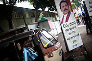 An auto rickshaw driver sits next to a picture celebrating Sri Lanka's President Mahinda Rajapaksa in Colombo, Sri Lanka, July 4, 2009. With the end of the 26 war between the Sri Lankan government and the LTTE, security in the capital city remains on high alert.