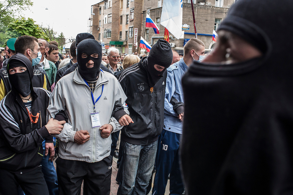 Pro-Russian activists guard the entrance to a local police station which was taken over by the crowd on Thursday, May 1, 2014 in Donetsk, Ukraine.