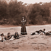 Group of men and women on a beach hamming it up for the camera. They have guns, books, fishing poles, pipes and a dog. vintage photo circa 1910.