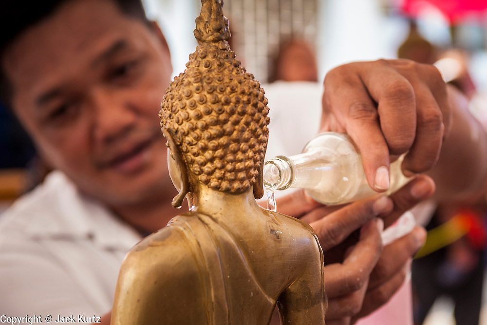 13 APRIL 2014 - BANGKOK, THAILAND: A man bathes a Buddha statue in scented oils at Wat Chana Songkram in Bangkok. Many people go to temples and religious ceremonies to make merit on Songkran. Songkran is celebrated in Thailand as the traditional New Year's Day from 13 to 16 April. Songkran is in the hottest time of the year in Thailand, at the end of the dry season and provides an excuse for people to cool off in friendly water fights that take place throughout the country. Songkran has been a national holiday since 1940, when Thailand moved the first day of the year to January 1.    PHOTO BY JACK KURTZ