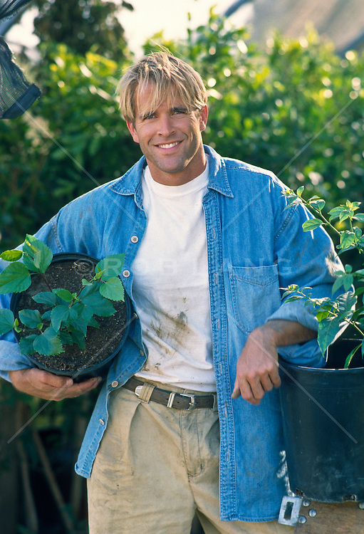 Blond man in a nursery holding plants