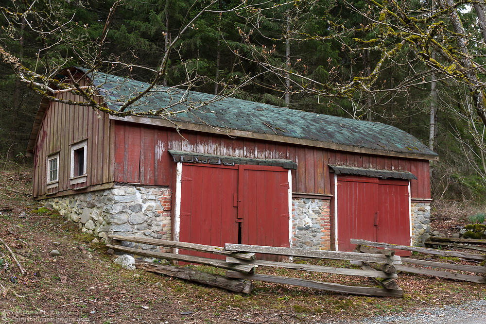 This barrel-roof shed was built between 1900 and 1910 by Richard Maxwell on his farm near Burgoyne Bay on Salt Spring Island, British Columbia, Canada.  The farm land is now part of Burgoyne Bay Provincial Park.  This shed was built for storage of larger farm equipment and has two, large access doors on the roadside of the building.  Photographed from Burgoyne Bay Road.