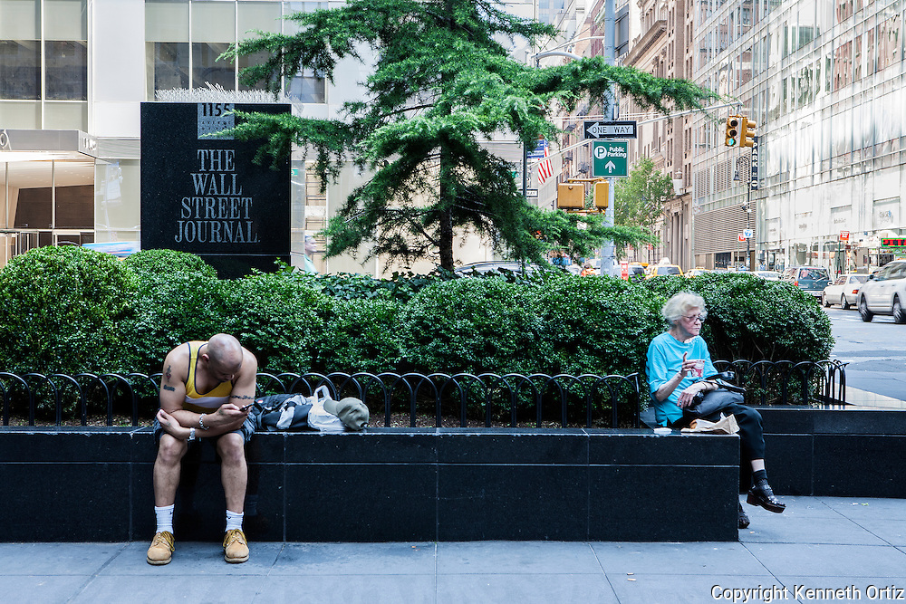 A man checks his phone messages while an elderly lady drinks her coffee on 6th Avenue and 44th Street.