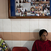 A pregnant woman (right) waits to meet the doctor under the board of photographs of previous western clients at the Akanksha Infertility and IVF Clinic in Anand, Gujarat, India. The centre has become the most popular clinic for outsourcing pregnancies by western couples.