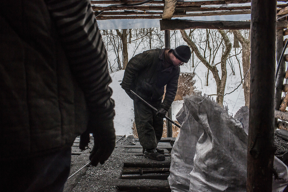 SNEZHNE, UKRAINE - JANUARY 25, 2015: Sergei Danshin, left, and Dmitry Kontratenko at the small private coal mine where they work in Snezhne, Ukraine. The mine produces approximately 15 tons of coal per day with a crew of four men. CREDIT: Brendan Hoffman for The New York Times