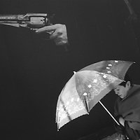 A woman walks past an advert using a hand and gun, Tokuyo, Japan, 2004