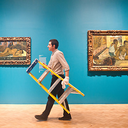 London, UK - 19 June 2013: An art technician called Jack walks with a ladder past ?Nevermore 1897? (L) and ?Te Rerioa (The Dream) 1897? (R) by Paul Gauguin at the Courtauld Gallery.